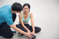 le coureur de femme tiennent sa jambe de cheville foulée par douleur Photo libre de droits