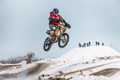 Le coureur en hauteur de moto sur la neige a couvert la colline Images stock