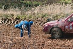 Le coureur examine le véhicule de dommages Photographie stock