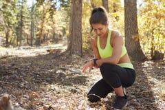 Le coureur féminin se met à genoux dans la forêt regardant le smartwatch Photos stock