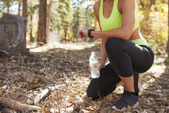 Le coureur féminin se met à genoux dans la forêt regardant le smartwatch, culture Photographie stock