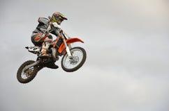 Le coureur spectaculaire de moto de saut sur une moto Image libre de droits