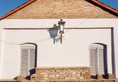 Le courrier antique de lampe sur le mur de briques avec deux a fermé des fenêtres Vieille maison Photographie stock libre de droits