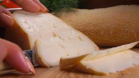 Le couteau a d?coup? un morceau du fromage du mouton mou banque de vidéos