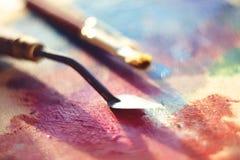 Le couteau de palette se trouve sur la palette, peinte avec des peintures à l'huile de rose, pourpre et rouge photos libres de droits