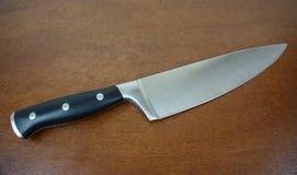 Le couteau du chef sur la partie supérieure du comptoir en bois Images stock