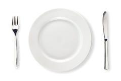 Le couteau, la plaque blanche et la fourchette ont isolé la première vue Photographie stock libre de droits