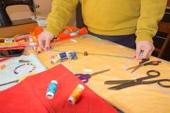 Le couturier coud une robe dans le studio Couturier faisant un modèle sur le morceau de tissu La machine à coudre se tient sur le Images stock