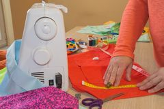 Le couturier coud une robe dans le studio Couturier faisant un modèle sur le morceau de tissu La machine à coudre se tient sur le Photographie stock