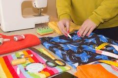 Le couturier coud une robe dans le studio Couturier faisant un modèle sur le morceau de tissu La machine à coudre se tient sur le Photographie stock libre de droits