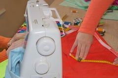 Le couturier coud une robe dans le studio Couturier faisant un modèle sur le morceau de tissu La machine à coudre se tient sur le Photo libre de droits