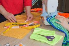 Le couturier coud une robe dans le studio Couturier faisant un modèle sur le morceau de tissu Main de femme sur la machine à coud Images stock