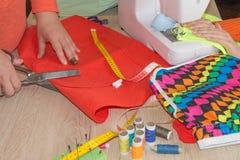 Le couturier coud une robe dans le studio Couturier faisant un modèle sur le morceau de tissu Main de femme sur la machine à coud Photos stock