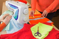 Le couturier coud une robe dans le studio Main de femme sur la machine à coudre Photos stock