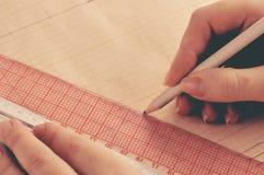 Le couturier de main développe un croquis de la robe Images stock