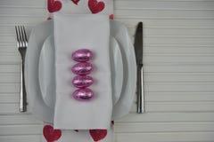 Le couvert d'horaire de Pâques dans le blanc avec du chocolat a enveloppé des oeufs et un tissu de modèle de coeur d'amour Photographie stock