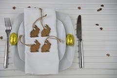 Le couvert de table de Pâques dans le blanc avec la couleur d'or jaune a enveloppé des oeufs et des décorations en bois de lapin Images libres de droits