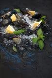 Le cozze crude fresche con il limone, le erbe e le spezie sullo scheggiato su ghiacciano il contesto scuro della pietra dell'arde fotografia stock libera da diritti