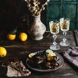 Le cozze cucinate con le coperture sono servito sul piatto con due vetri di vino bianco Fotografia Stock