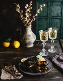 Le cozze cucinate con le coperture sono servito sul piatto con due vetri di vino bianco Fotografie Stock