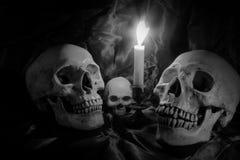 Le crâne avec le groupe de fleurs et la bougie s'allument sur la table en bois avec le fond noir dans la nuit dans le St noir et  Images stock