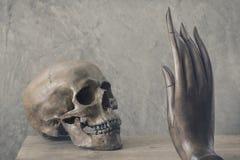 Le crâne confrontent avec la main Image libre de droits