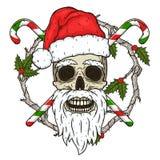 Le crâne de Santa Claus à l'arrière-plan des branches de l'omella et des sucreries croisées Crâne de Santa Claus Photos libres de droits