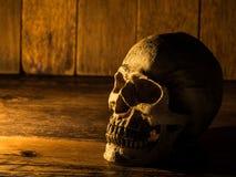 Le crâne est placé sur un bureau en bois Bougie de fond latéral et en bois Image stock