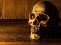 Le crâne est placé sur une table en bois Le fond est un plat et une lumière en bois de la bougie au crâne Images stock