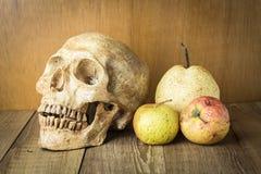 Le crâne et la gâchette portent des fruits la vie immobile sur le fond en bois photographie stock