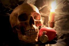 Le crâne humain avec l'horloge de poche de vintage, le coeur rouge et la bougie s'allument sur le fond de tissu, l'amour et le co Photographie stock