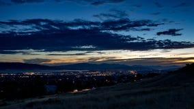 Le crépuscule tombe au-dessus d'une ville somnolente dans une vallée avec des montagnes et d'un lac à l'arrière-plan photographie stock libre de droits