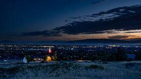 Le crépuscule tombe au-dessus d'une ville somnolente dans une vallée avec des montagnes et d'un lac à l'arrière-plan images libres de droits