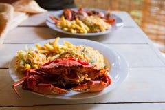 Le crabe bouilli sur la table en bois, les crabes cuits du plat blanc a servi avec la hausse et les pommes frites, vue supérieure photo libre de droits