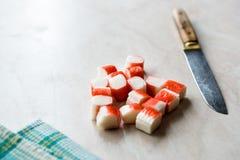 Le crabe découpé en tranches colle des tranches de Surimi sur la surface de marbre tout préparé photo libre de droits