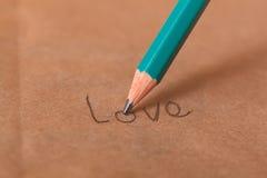 Le crayon écrit l'amour de mot sur un papier Photographie stock libre de droits