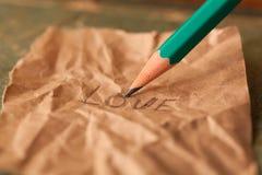 Le crayon écrit l'amour de mot sur un papier Images libres de droits