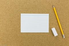 Le crayon et la gomme avec le papier sur le liège embarquent Image libre de droits