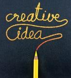 Le crayon jaune écrivent le mot créatif d'idée sur le papier noir de métier Images stock