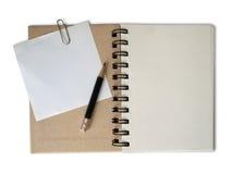Le crayon noir de projectile réutilisent en fonction le cahier de papier Photographie stock libre de droits