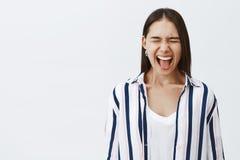 Le cri comme personne entendent Portrait alimenté d'entrepreneur féminin élégant bel dans le chemisier rayé, yeux fermants et photographie stock libre de droits