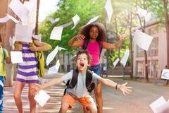 Le cri perçant très enthousiaste de garçon avec des amis jette le papier Photographie stock libre de droits
