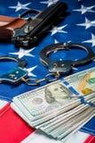 le crime et la punition ont saisi l'argent et les armes sur le drapeau américain photographie stock