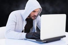 Le criminel de Cyber entaille d'un ordinateur portable images stock