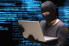 Le criminel de Cyber entaille d'un ordinateur portable sur le fond de pluie de code de matrice images stock