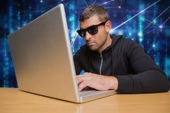 Le criminel de Cyber portant les lunettes noires entaille d'un ordinateur portable sur un bureau contre le CCB de pluie de code d photo libre de droits