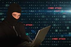 Le criminel de Cyber portant une huée entaille sur l'ordinateur portable sur le fond de pluie de code de matrice images stock