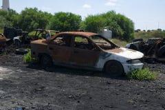 Le criminel de guerre chante la voiture abandonnée brûlée après bombardement de la ville Images stock