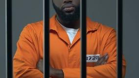 Le criminel noir avec des mains a croisé la position en cellule de prison, attendant le jugement banque de vidéos