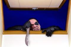 Le criminel s'élève dans la maison par une fenêtre ouverte Photographie stock libre de droits